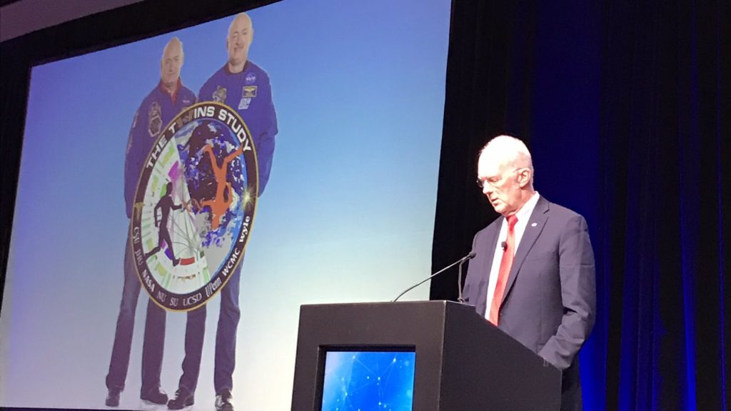 Image of Dr. John Charles (NASA, retired) along with a photo of Mark and Scott Kelly, astronauts